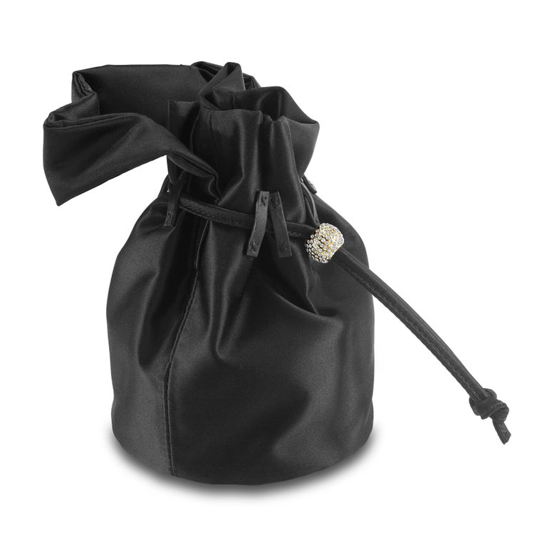 The Grace Mini is featured in our Black Onyx satin. This soft pouch has a satin handle and drawstring closure. The closure is embellished with Swarovski crystals and gold hardware. It fits the large iPhone, has interior card slots and features our