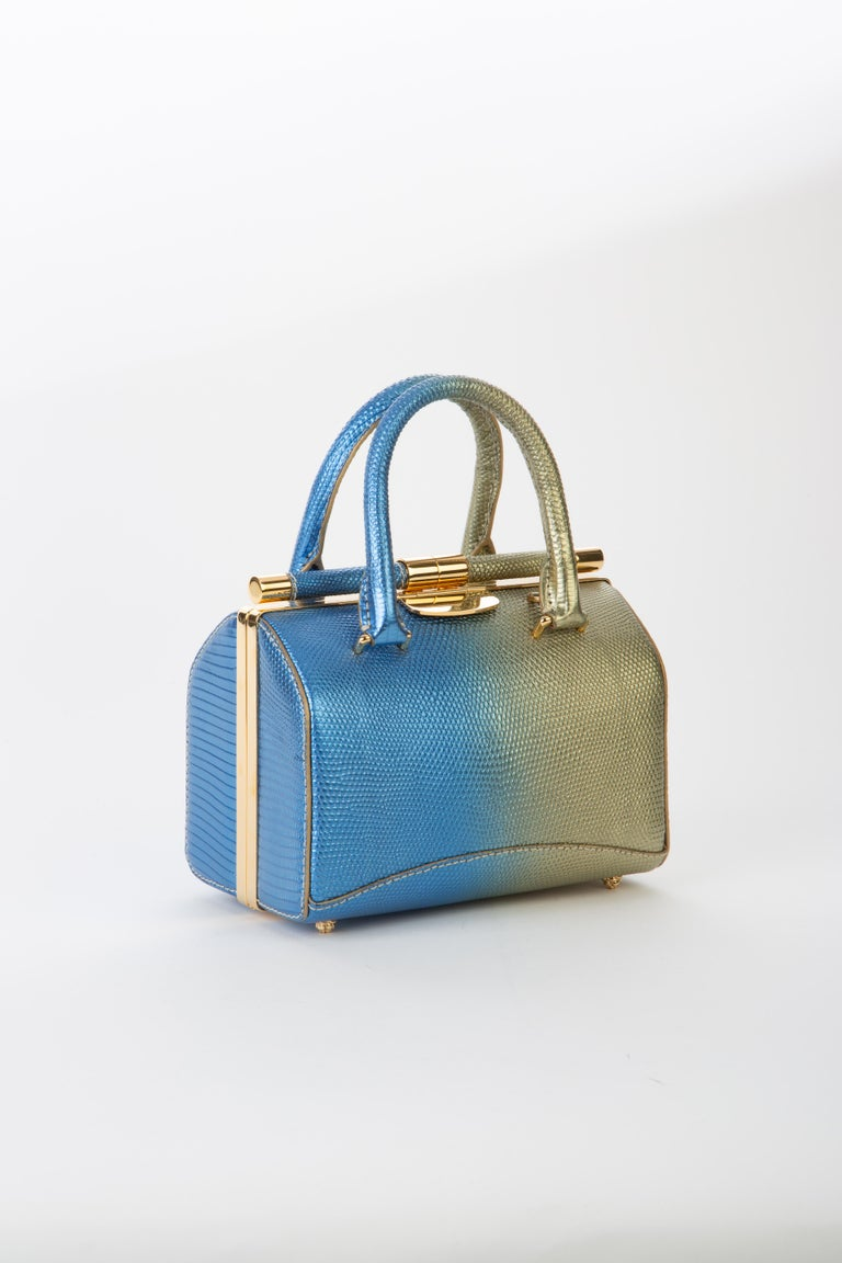 """The Jamie Doctor is a double handle structured bag. It features our slide-lock closure, pinecone feet, interior pocket and our signature Thayer blue suede lining.   Size: Small Hardware: Gold Interior/Lining: Suede Dimensions: 7.5"""" W x 5.0"""" H x 4.0"""""""