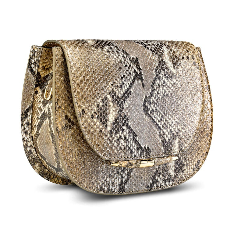 The Jane Saddle Small is featured in Metallic Gold Natural Python with gold hardware. The handbag is designed with a rounded three-quarter front flap, a magnetic snap closure and our custom Infinity Bar. It has a hidden exterior pocket, an optional