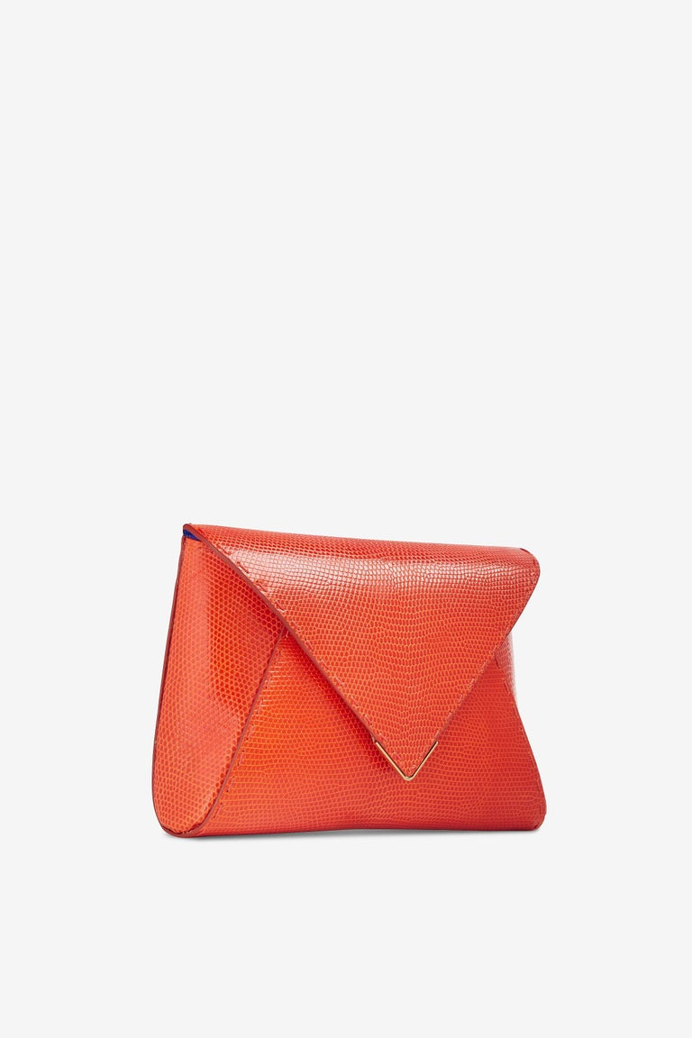 The Lee Pouchet Small Bright Orange Lizard Gold Hardware is a soft clutch designed with a triangular front flap and a magnetic closure. It features a hidden exterior pocket, a detachable gold cross-body chain and our signature Thayer blue satin