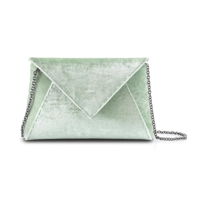 The Lee Pouchet Small is featured in our Pistachio crushed velvet with gunmetal hardware. The envelope-shaped clutch is designed with a triangular front flap and a magnetic snap closure. The Lee fits the large iPhone, has a hidden exterior pocket,