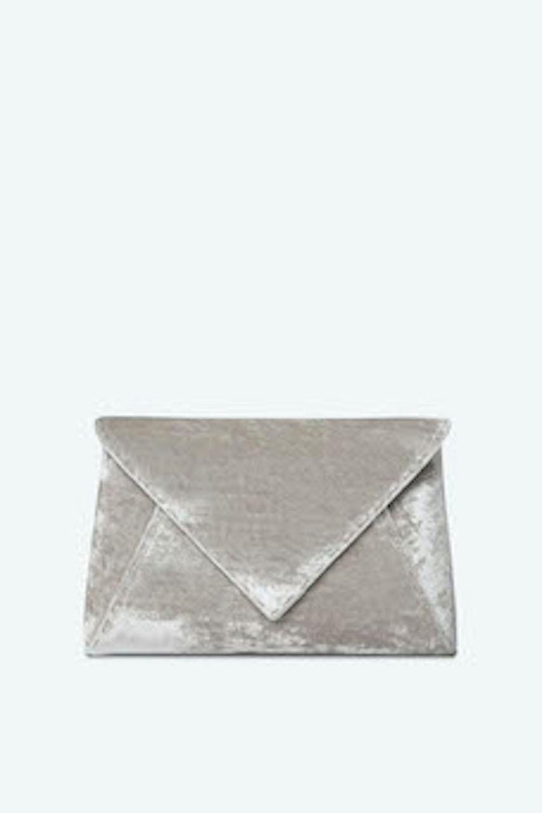 The Lee Pouchet Small is featured in our Platinum crushed velvet with silver hardware. The envelope-shaped clutch is designed with a triangular front flap and a magnetic snap closure. The Lee fits the large iPhone, has a hidden exterior pocket, an