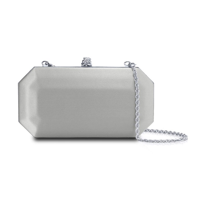 The Perry Small is featured in our Platinum satin with silver hardware. The Perry is a hard-framed clutch designed with interior pockets and an optional silver cross-body chain. It's elegant emerald shape is inspired by Tyler's own engagement ring