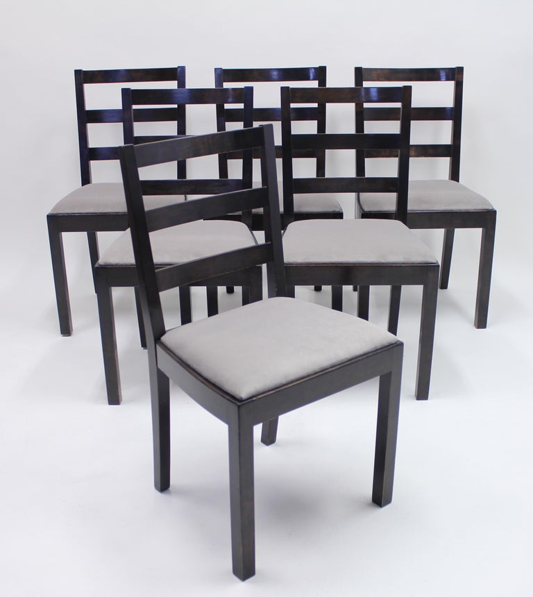 Set of six Typenko chairs designed by Axel Einar Hjorth in 1931 for Nordiska Kompaniet. Frame of dark stained birch with new light grey velvet upholstery. All of the chairs have the original metal plack from the manufacturer. The present model is