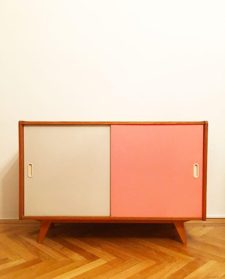 Original vintage cabinet with white sliding doors. Type U-452, manufactured in the 1960s by Interier Praha, designed by Jiri Jiroutek. Wooden construction. Dimensions: 110 × 78 × 45 cm (W × H × D) Manufacturer: Interier Praha Country: