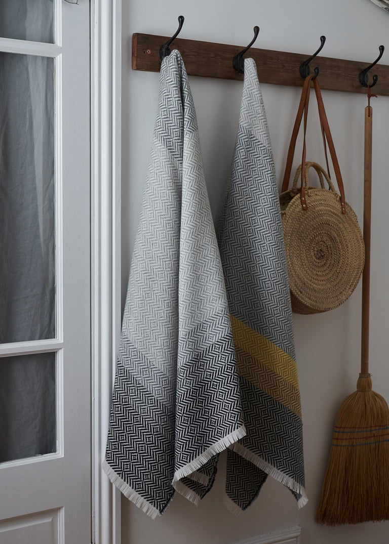 Drawing inspiration from the color and pattern found in stain glass work, the Uccle block throw takes its name from an area of Brussels renowned for its Art Deco architecture.  Woven in blocks of grey and pearl grey melange with a deep border of