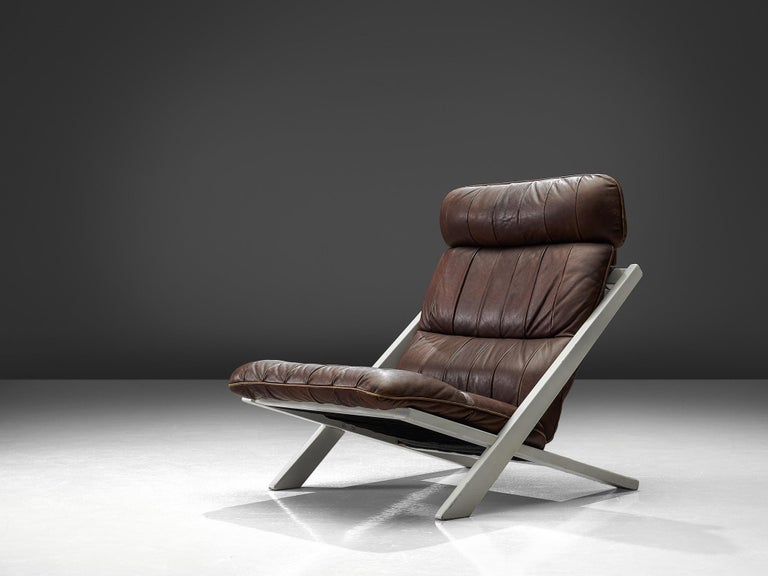 Ueli bergère for De Sede, lounge chair, Switzerland, 1970s.  High back lounge chair by de Swiss quality manufacturer De Sede. The X-shaped frame consists of black lacquered wood. This makes an interesting contrast to the warm patinated cognac