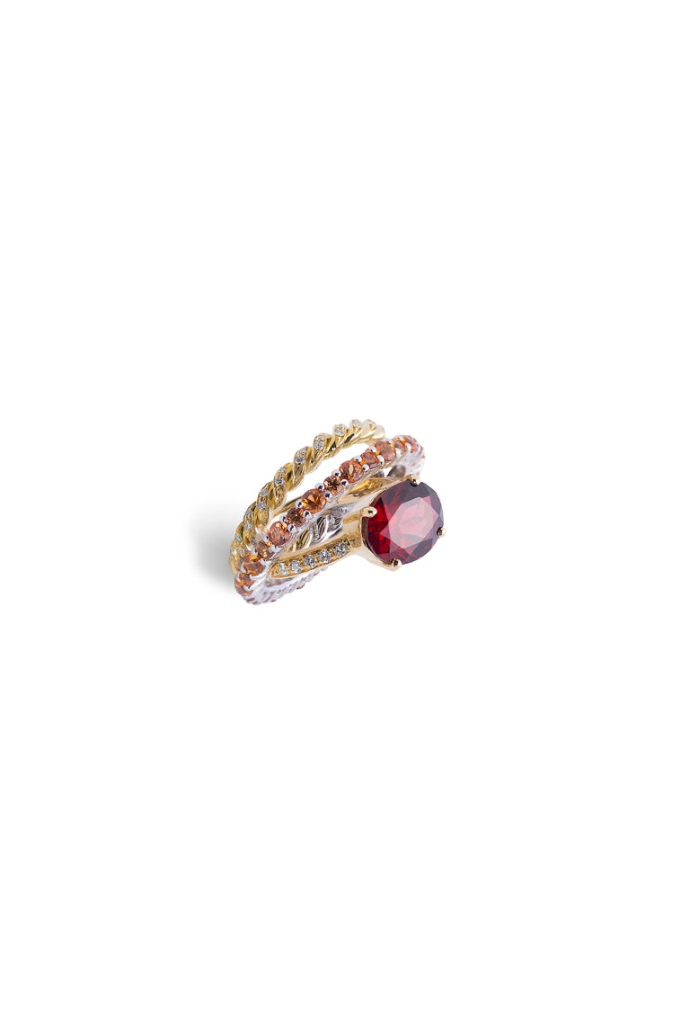 Here there is an amazing Aura ring, handcrafted with pure 18 karats yellow gold adorned with deep red garnet and powerful 3 karat tangerine sapphires and 0.23 karat white diamonds. A ring made of three crossed gold threads touching each other