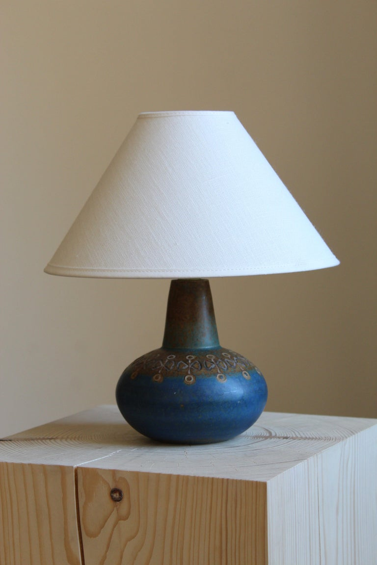 A table lamp by Ulla Winblad. Handcrafted in stoneware by Allingsås Keramik, Sweden, c. 1950s  Sold without lampshade. Stated dimensions exclude lampshade. On request and pending availability, illustrated linen lampshade can be included.