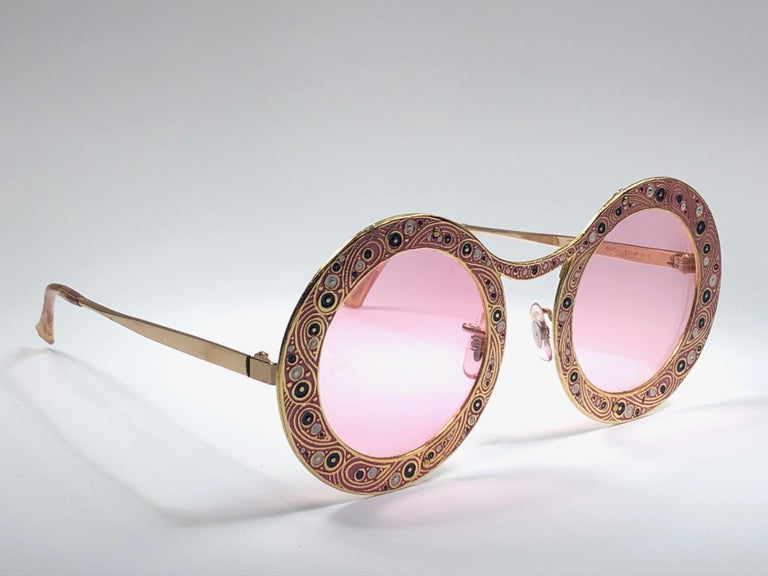 Ultra rare pair of Christian Dior Sunglasses circa 1969.  This is a seldom and rare piece not only for its aesthetic value but for its importance in the sunglasses and fashion history.   Delicate enamel ornamented plated frame.  Please noticed this