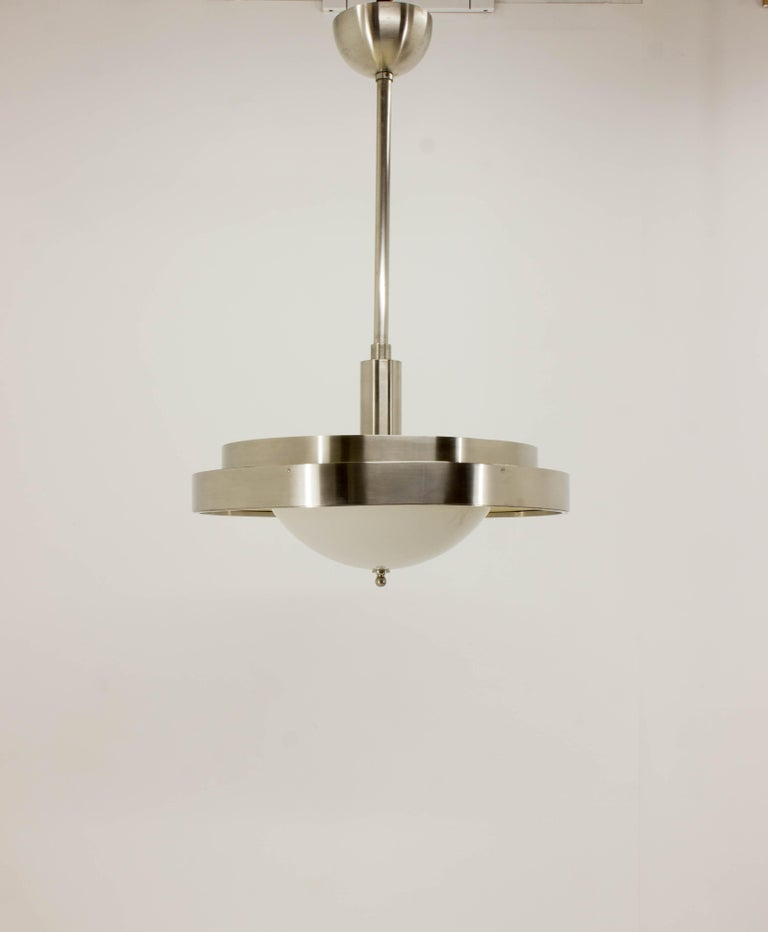 This unique nickel plated Bauhaus chandelier from 1930s was in property of Czech architect and it is in a very good condition. It has two separate circuits - upper with four and lower with three bulbs. It was carefully cleaned, repolished and