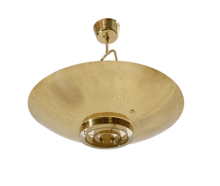 Decorative and iconic scandinavian ceiling light in brass. Designed and Paavo Tynell for Taito in 1950 and made in Norway on licence/permit by Arnold Wiig's Fabrikker from circa 1950s second half. This lamp is called the 'United Nations' model