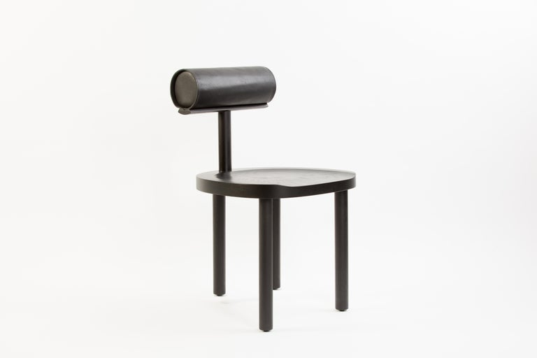 UNA dining chair in black stained oak with black leather back bolster. The UNA chair intersects the round wooden seat and legs with a leather upholstered cylindrical back. Using these fluid shapes allows greater focus on the details of the wood
