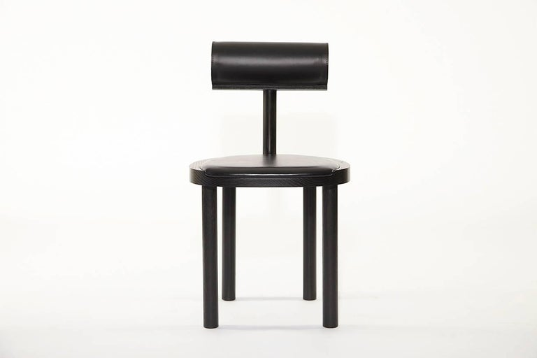 UNA Leather Upholstered Dining Chair in Black Stained Oak intersects the round wooden seat and legs with a leather upholstered cylindrical back. Using these fluid shapes allows greater focus on the details of the wood grain and pristinely stitched