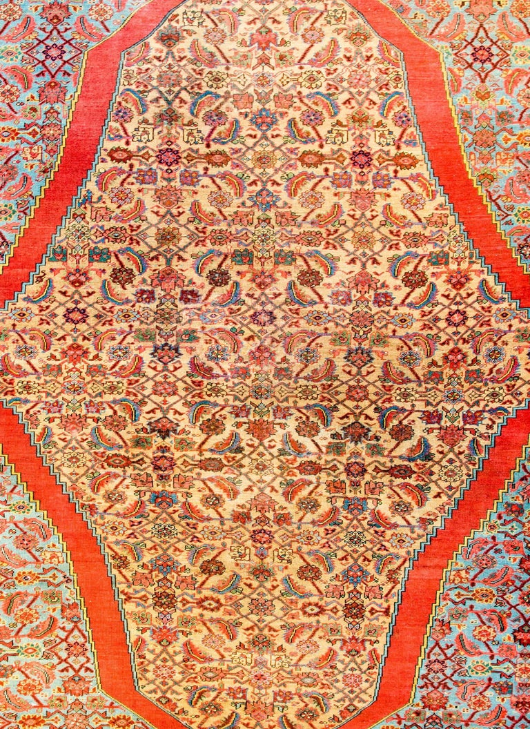 An unbelievable early 20th century Persian Bakshaish rug with an incredibly all-over trellis and floral pattern woven in crimson, pink, green, gold and dark indigo on a natural undyed wool background. The trellis floats in a large, wide crimson