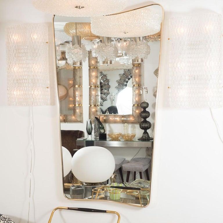 Undulating rectangular mirror with brass surround.
