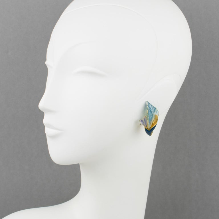 Elegant Emanuel Ungaro Paris signed clip-on earrings. Gilt metal floral shape in an Art Nouveau inspired design with metal topped with cobalt blue enamel and compliment with iridescent resin fan shape. The resin fan looks pretty much like pate de