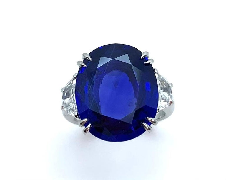 This platinum ring features a rare, natural color, gem Ceylon blue sapphire set with two half-moon diamonds. The sapphire is accompanied by Gemological Institute of America Origin and American Gemological Laboratory Prestige Reports stating the