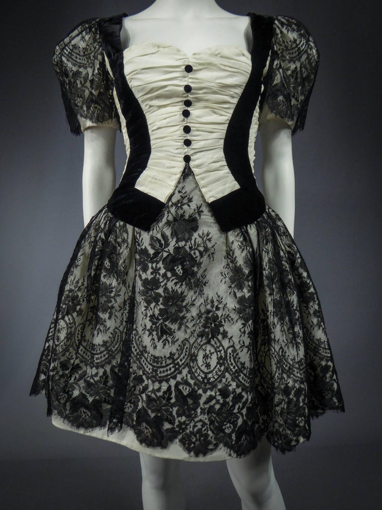 Circa 1980/1990  France  Black and white cocktail dress with bustier, unidentified Haute Couture from the 80s / 90s. Large pleated neckline of white taffeta and black velvet. Short puff sleeves and skirts in the form covered with a lace of calais
