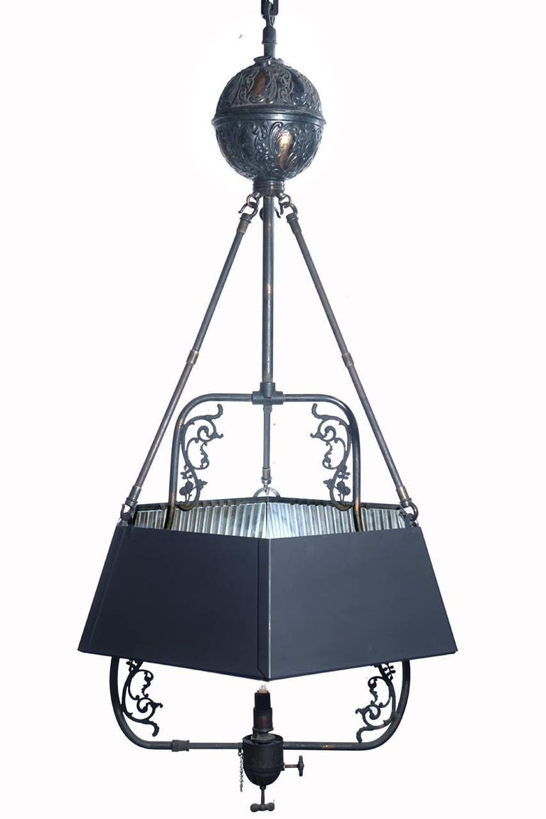 This is a very early fuel lamp. It dates before the use of piped gas and electric. It has been wired to take a standard base bulb but still retains the tank, valve, original finish and decorative details. There is a beautiful mirrored hexagonal