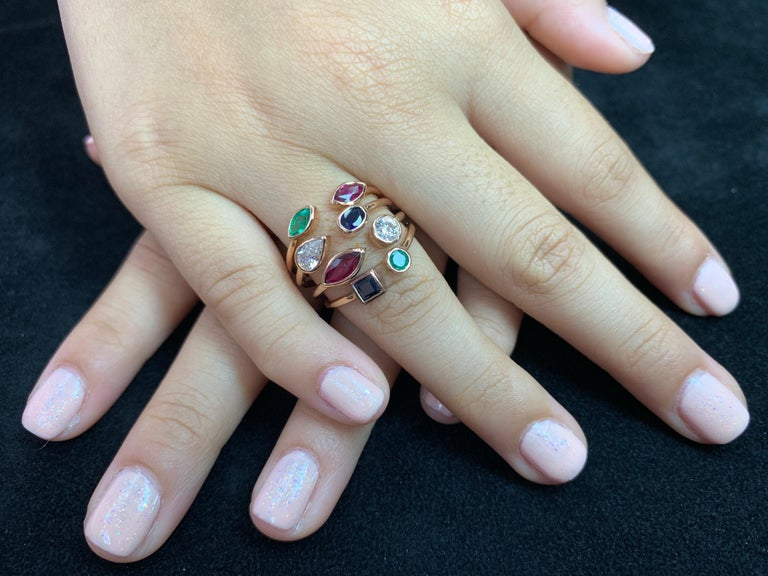 Here is a unique multi stone ring. The ring is set in 18k rose gold with emeralds, sapphires, rubies and diamonds. There are a combination of 2 of each precious stones of various sizes that make up this ring. Diamonds 0.47 cts. Rubies and sapphires