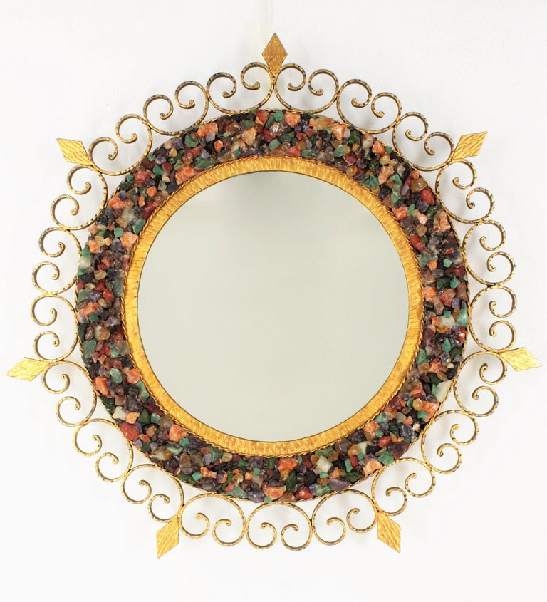 Unusual illuminated sunburst shaped mirror with colorful natural small gemstones mosaic covering the central part surrounding the glass. The frame has encrusted beautiful gemstones, including jade, malamute, tiger's eye, aventurine, smoky quartz,