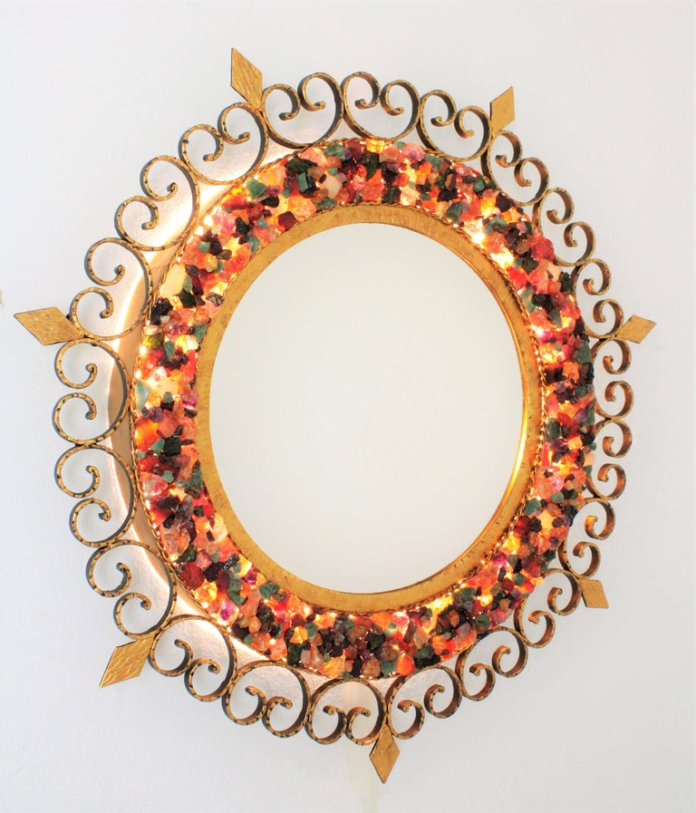 Unusual retro illuminated gilt iron sunburst mirror with colorful natural small gemstones mosaic covering the frame. Spain, 1960s. The frame has encrusted beautiful gemstones surrounding the glass: including jade, malamute, tiger's eye, aventurine,