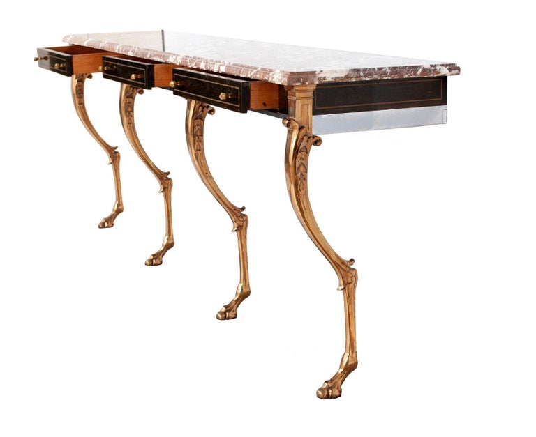 Unique custom 1970s Hollywood Regency sideboard, console or server with Rosso Levanto marble top on four heavy solid stylized brass animal form legs with hoofed feet and nickel frame with three ebonized rosewood drawers, having brass inlay and