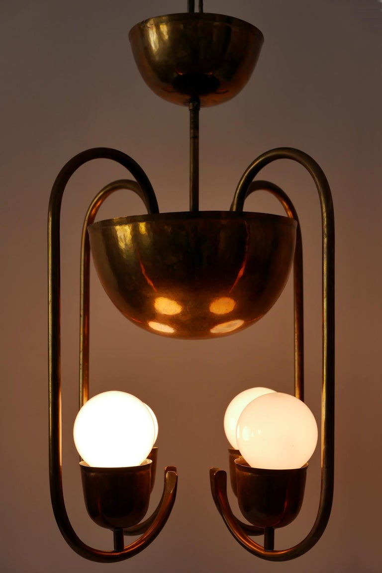 Unique work of the famous Bauhaus metal artist Hayno Focken: four-armed Bauhaus / Art Deco chandelier or pendant lamp in hammered solid brass. Probably a custom work in 1930s, Lahr, Germany. Makers mark to the canopy (see the last image).  Hayno