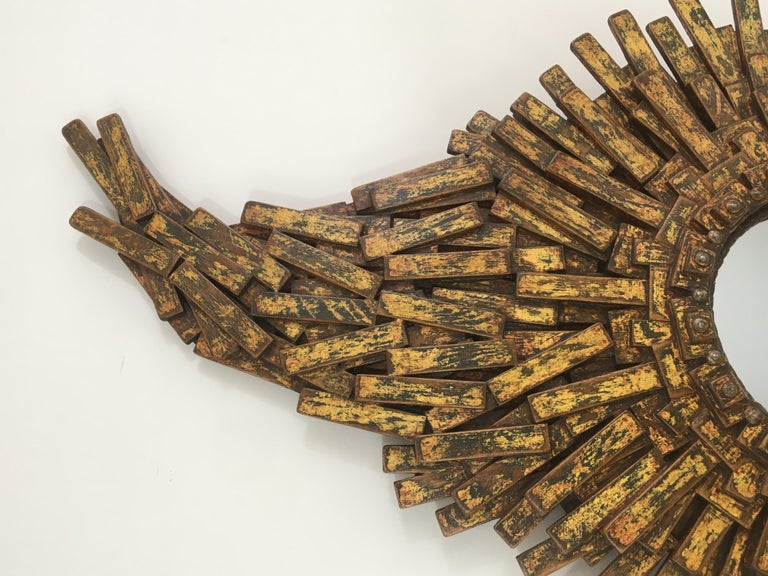 This unique amazing Brutalist mirror is made of painted wood, rope & old iron nails. This is a fantastic work of art made of hundreds of oak pieces representing a large sunburst mirror with a flame on top of it. The quality of this creation is