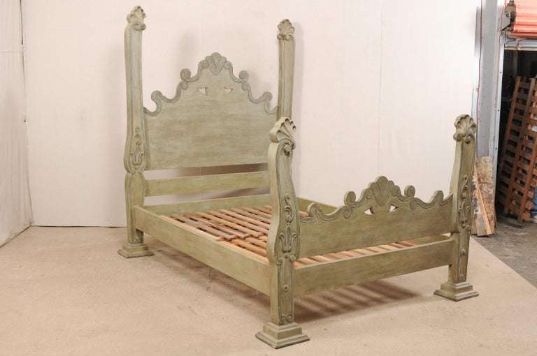 A Brazilian hand carved and painted wood queen bed from with tall head and foot boards. This impressive queen bed, made from tropical hard wood, features a substantial headboard with arch shaped center in a fluid motion of scrolls and pierced