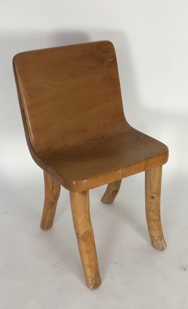 One of a kind chair, a true conversation piece. The body of the chair is carved from a solid piece of teak and the solid legs have been added. Unique in design. Solid, and ideal for either inside or out. The artist has created three of these chairs,