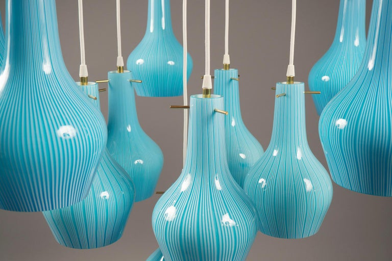 Eleven-light suspension fixture, featuring eleven Vintage Venini shades in light blue with white striations, suspended from a brass structure. Height adjustable.