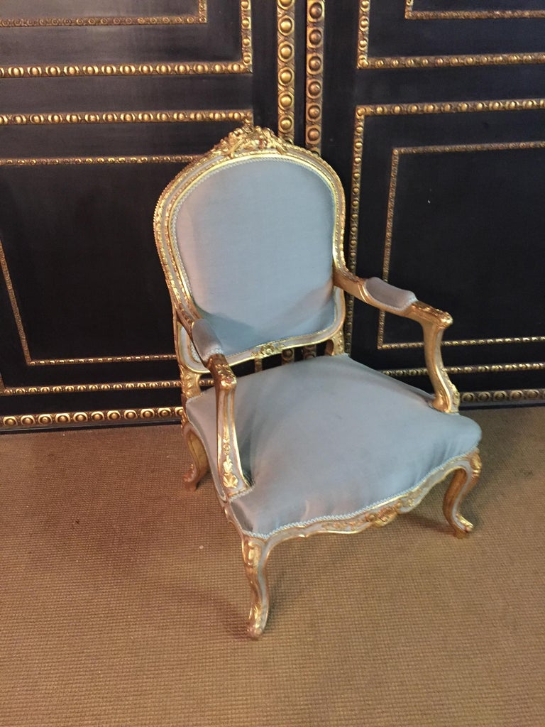 Solid beechwood, carved, colored and gilded. Semicircular rising backrest frame with rocaille crowning. Appropriately curved, carved frame. Slightly curved frame on curly legs. The seat and backrest are finished with a historic, classic upholstery,