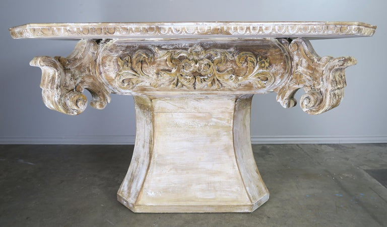 Unique painted dining or center table with a beautiful white washed finish, 1930s. The table has a slight rectangular shaped top with straight corners and an egg and dart carved detail along the edge. The top is supported by an eight sided