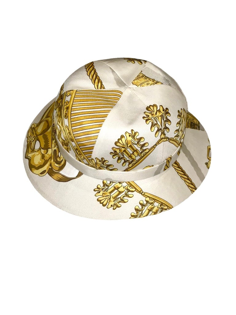 Beautiful HERMES printed silk twill structured safari hat  Unique, rare piece Off white background with gold Greek Scythian art jewelry print throughout Fully lined in white silk Made in France Dry clean only  Rare print by Hermès