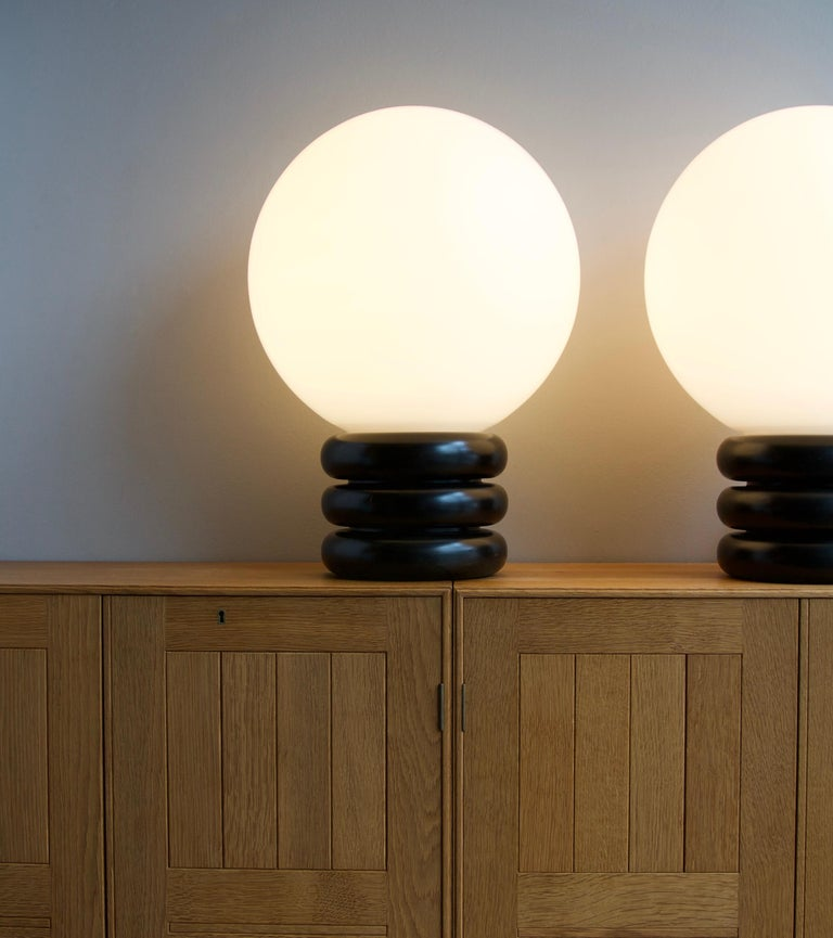 A pair of vintage Czech table lights in turned wood and mouth-blown opal glass, designed and made by Antonín Hepnar, circa 1975. The materials traditionally associated with the Czech Republic are glass and porcelain. However, Hepar has worked