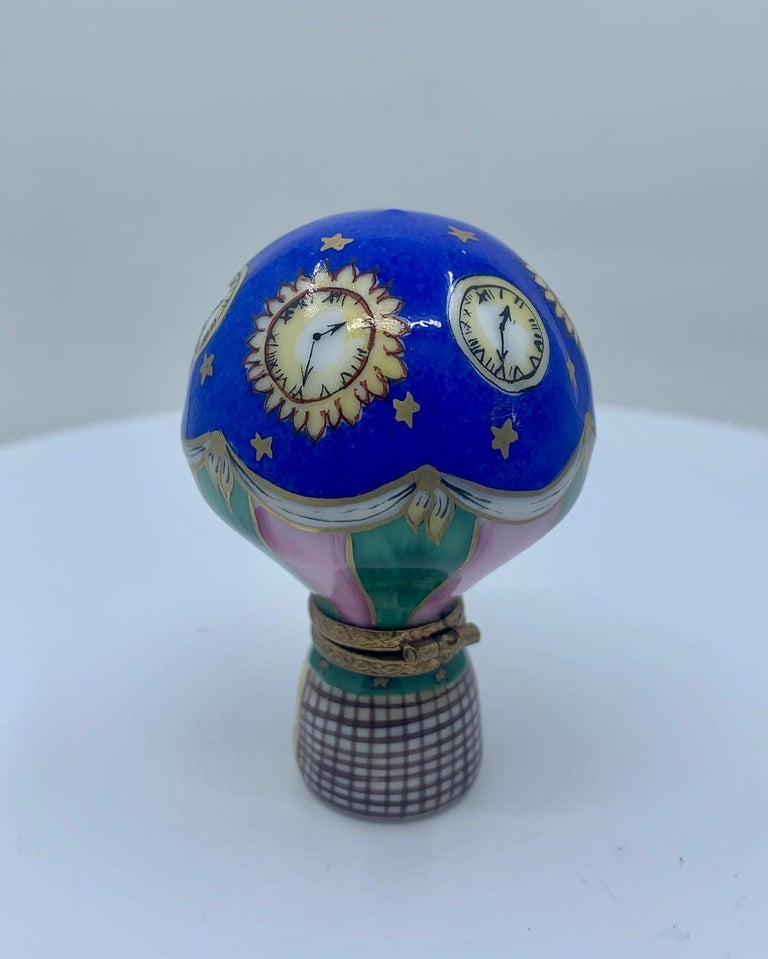 Collectible and unique, Limoges Rochard porcelain miniature trinket box is handmade and hand painted in France and features a very detailed vivid cobalt blue hot air balloon with celestial gold stars and four sun clocks interspaced between round