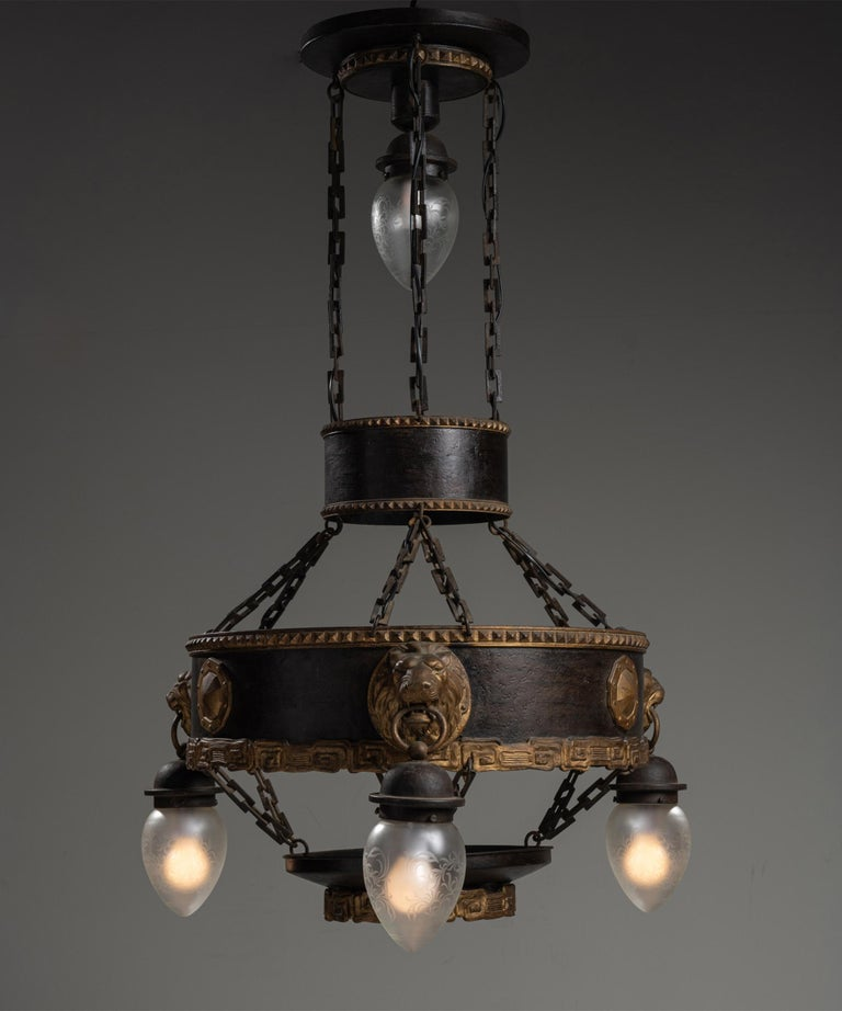 Unique metal chandelier, France, circa 1920  Iron chandelier with gilt framework, and lions heads holding etched glass pendants.  Measures: 29.5