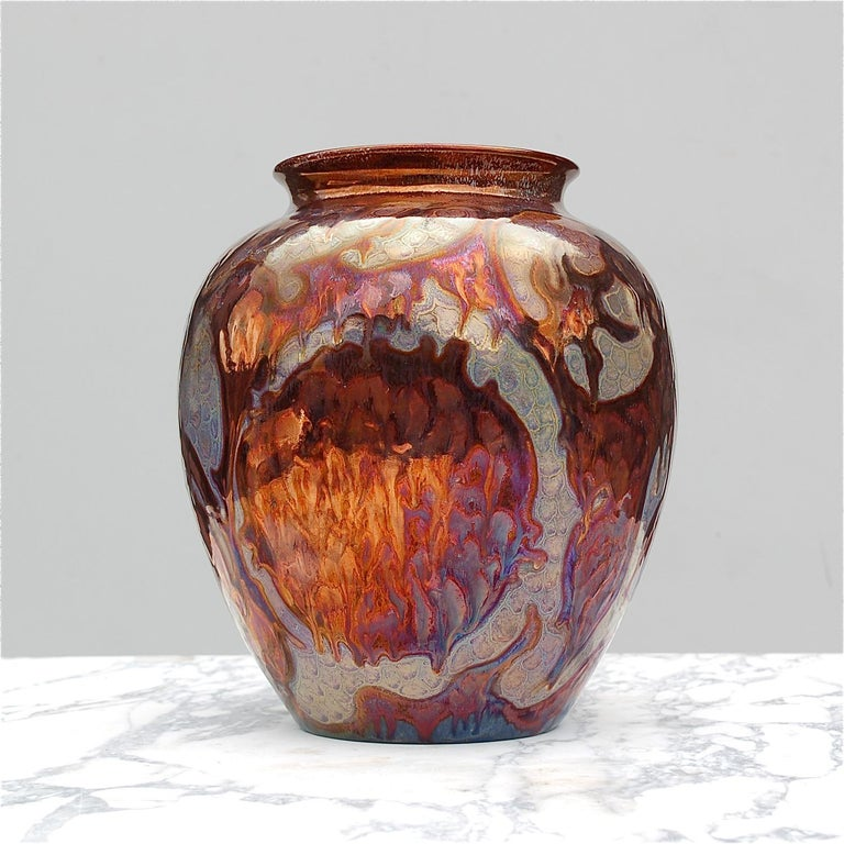 Exceptional earthenware lustre vase with a mesmerising, iridescent glaze. The different shades and metallic tints flow into each other and depending on how the light captures the vase, the reflection changes and with it the color tone, making it