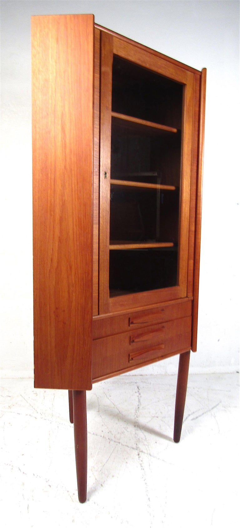 This stunning vintage modern Danish corner cabinet features three shelves and three small drawers on the base. An unusual design that can fit comfortably in any corner of the room. A glass-front cabinet door allows this to function as a display