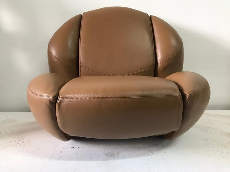 Expertly restored and reupholstered in fine leather (camel tone), this vintage 1960s unique and sculptural Italian chair by Comfortline, Italia rocks and sits adults comfortably. Original label retained.  Note: We recommend this chair sits on a