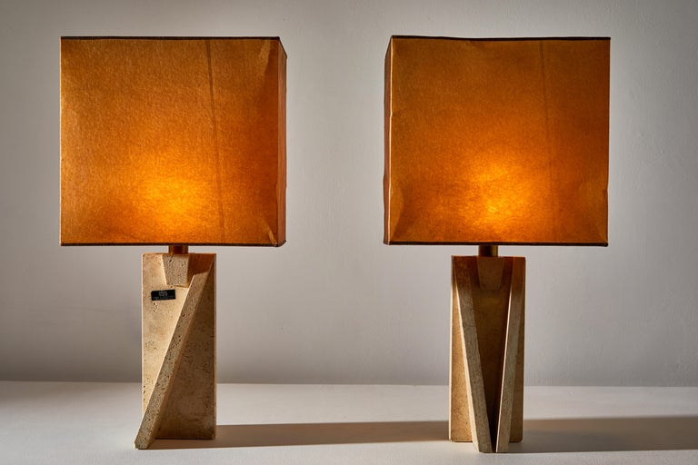 Unique pair of table lamps by Cerri Nestore. Designed and manufactured in Italy, circa 1970s. Travertine with original shades, brass hardware. Retains manufacturers label. Original cord. Each light takes one E26 100w maximum bulbs. Bulbs provided as