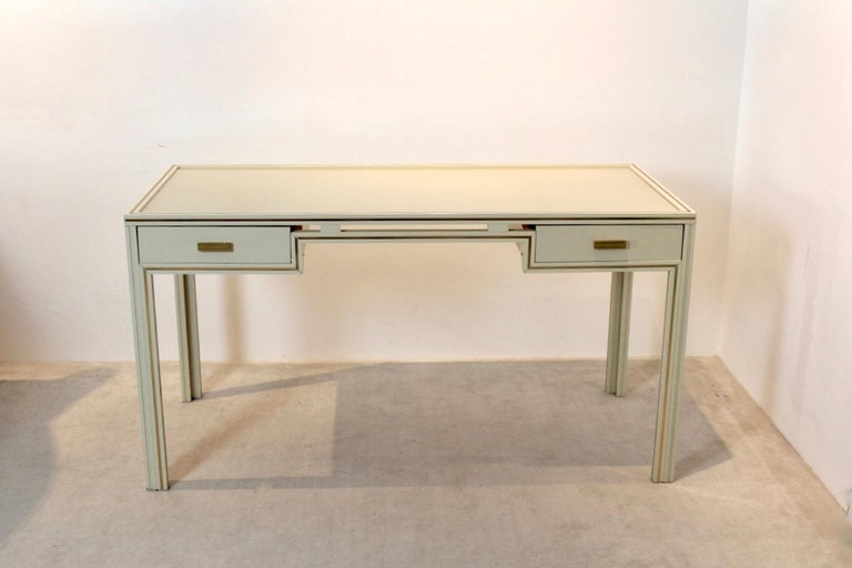 Unique Pierre Vandel Paris cream lacquered French desk made from aluminum and glass. In cream aluminium with beautiful Gold accents. Featuring two drawers and glass tier. With some light wear due to age and use. Pierre Vandel was a French interior