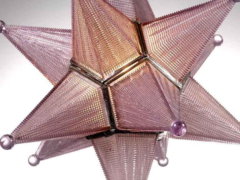 We have never come across a star lamp of this quality. Each star section is cast prismatic glass. The glass also has a lavender cast to it. The tint happens over years of use and is part of the patina and aging process for some types of glass. The
