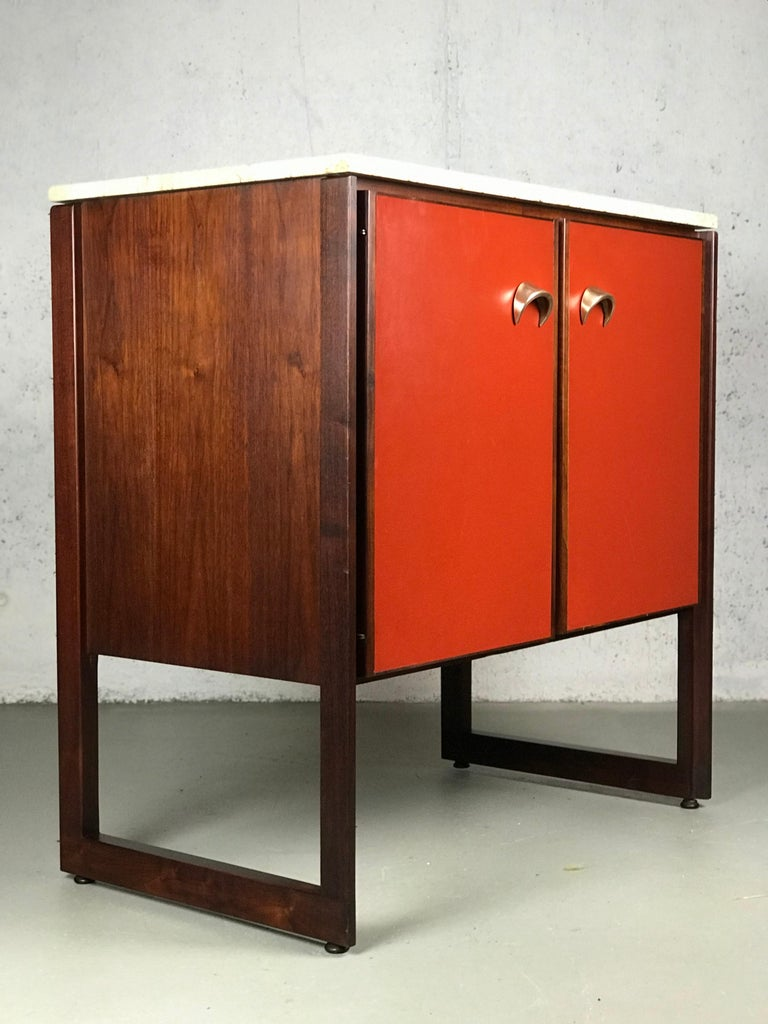 Wonderful example of American modernism by Jens Risom. This cabinet is made of an array of contrasting materials: walnut, rosewood, travertine marble, red vinyl and brass. Rosewood is used in the trim around the doors, framing pieces and legs. There