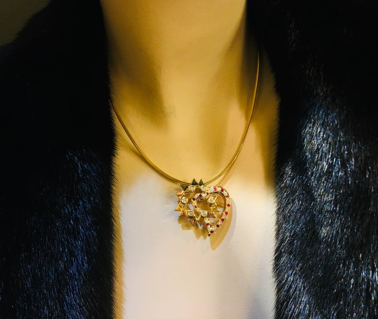 Very unique pendant or brooch pin with a modern artisan style features a 10 pointed star or decagram, embellished with 6 round diamonds bezel set in 14 karat yellow gold and intersected by a stylized ruby and diamond pave heart.  Please note a chain