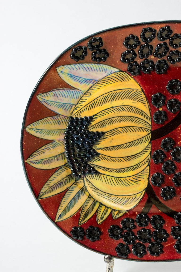 Amazing, unique stoneware platter by Birger Kaipiainen in an oval form. Beautiful composition of yellow sunflowers against a rich red background, surrounded by a pattern of round black seeds in relief.