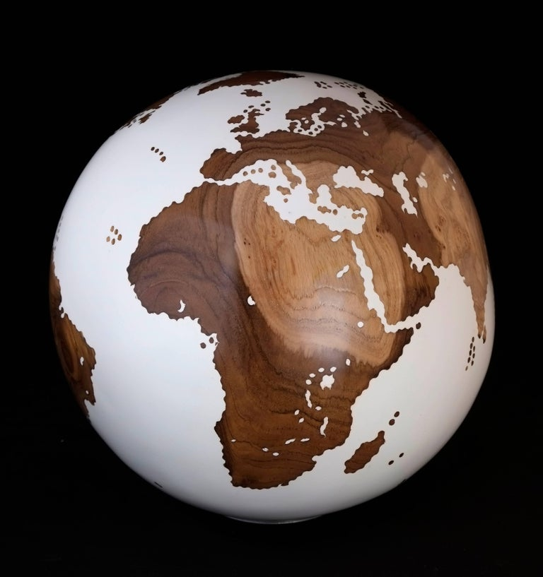 Unique hand-carved wooden globe made of reclaimed teak root with classic acrylic white resin finishing.  The continent parts show magnificent natural textures of the wood's layers.  Dimension: 9.84 inches / 25 cm Materials: Reclaimed teak root,