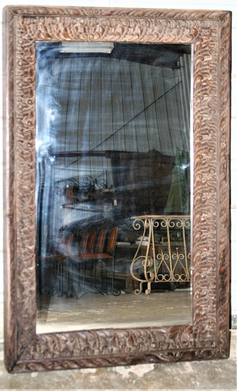 No other mirror frame can match this unique highly carved teak wood frame that comes from a custom made colonial era home. The front is carved all over. The age and patina of the wood and the meticulous carvings on the frame can be only appreciated